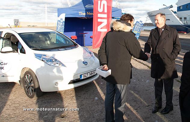 Siim Kallas next to a Nissan Leaf